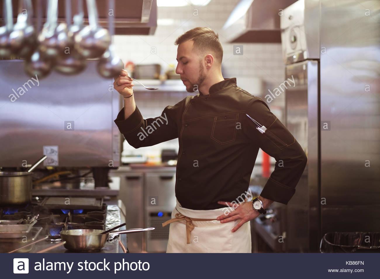 Concept alimentaire. Un jeune cuisinier se tient dans la cuisine et prépare un plat. Photo Stock