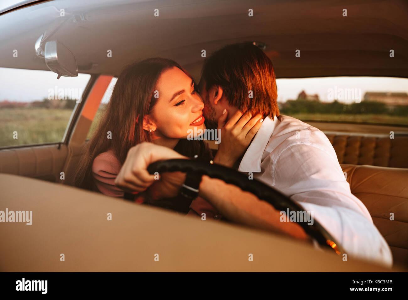 Jeune beau couple tout en restant assis à l'intérieur d'une voiture Photo Stock