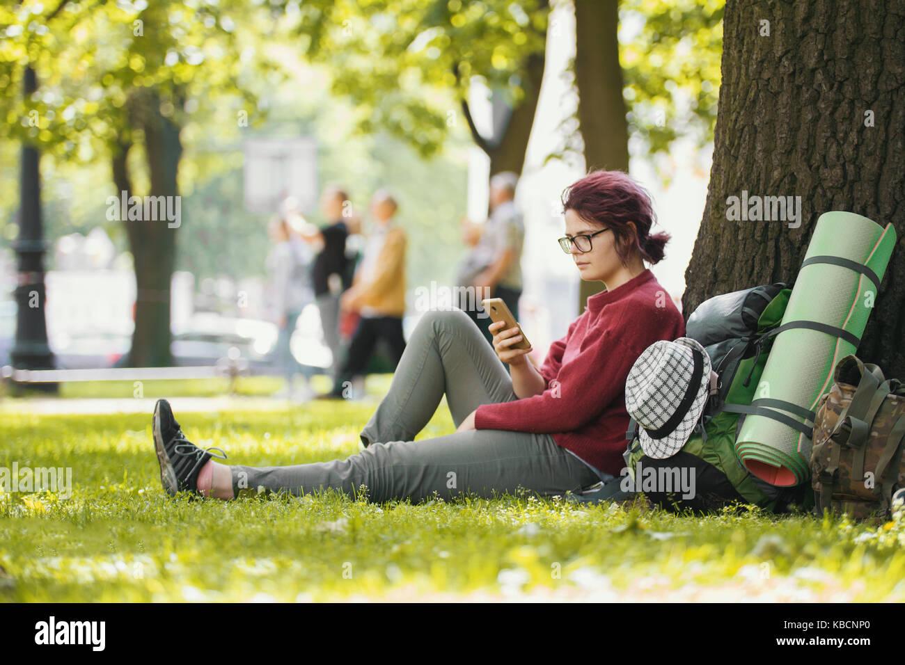 Sac à dos fille adolescente avec tourisme looking at smartphone in city park Photo Stock