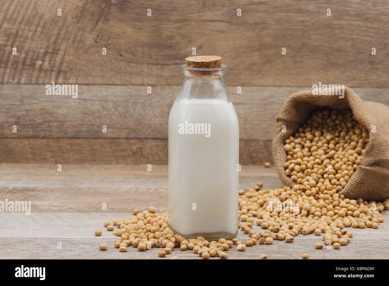 Bouteille de lait de soja et de soja sur table en bois Photo Stock