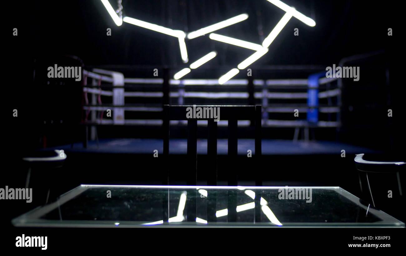 Ring de boxe et deux chaises avec table fond sombre. Vue sur un ring entouré de cordes spotlit bleu par un Photo Stock