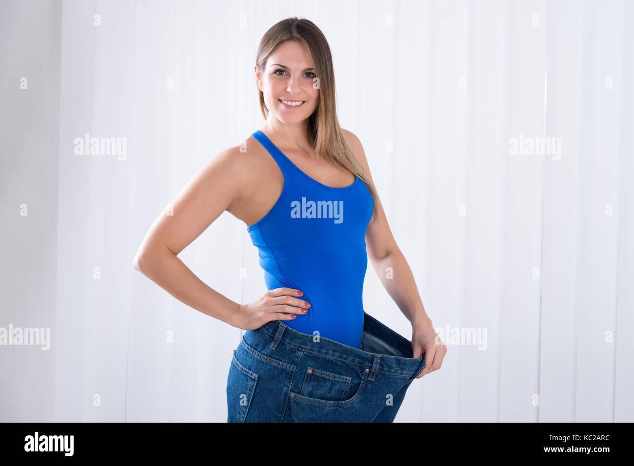 Happy young woman showing her amaigrissement en portant des vieux jeans Photo Stock