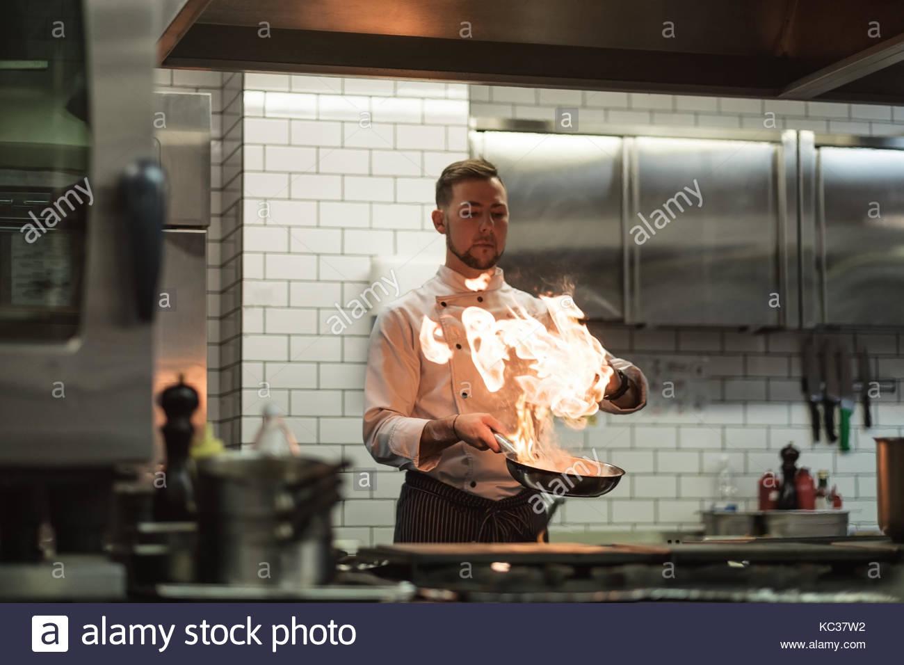 Un homme cuit la cuisson friteuses dans un feu de cuisine. Photo Stock