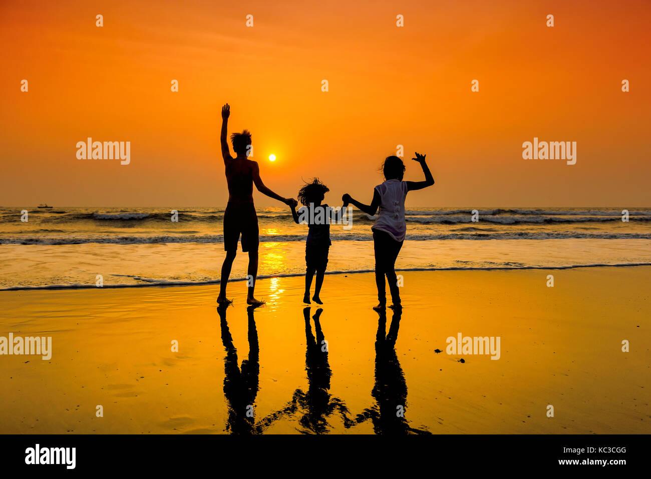 Silhouettes d'un groupe d'enfants danser sur la plage au coucher du soleil. Photo Stock