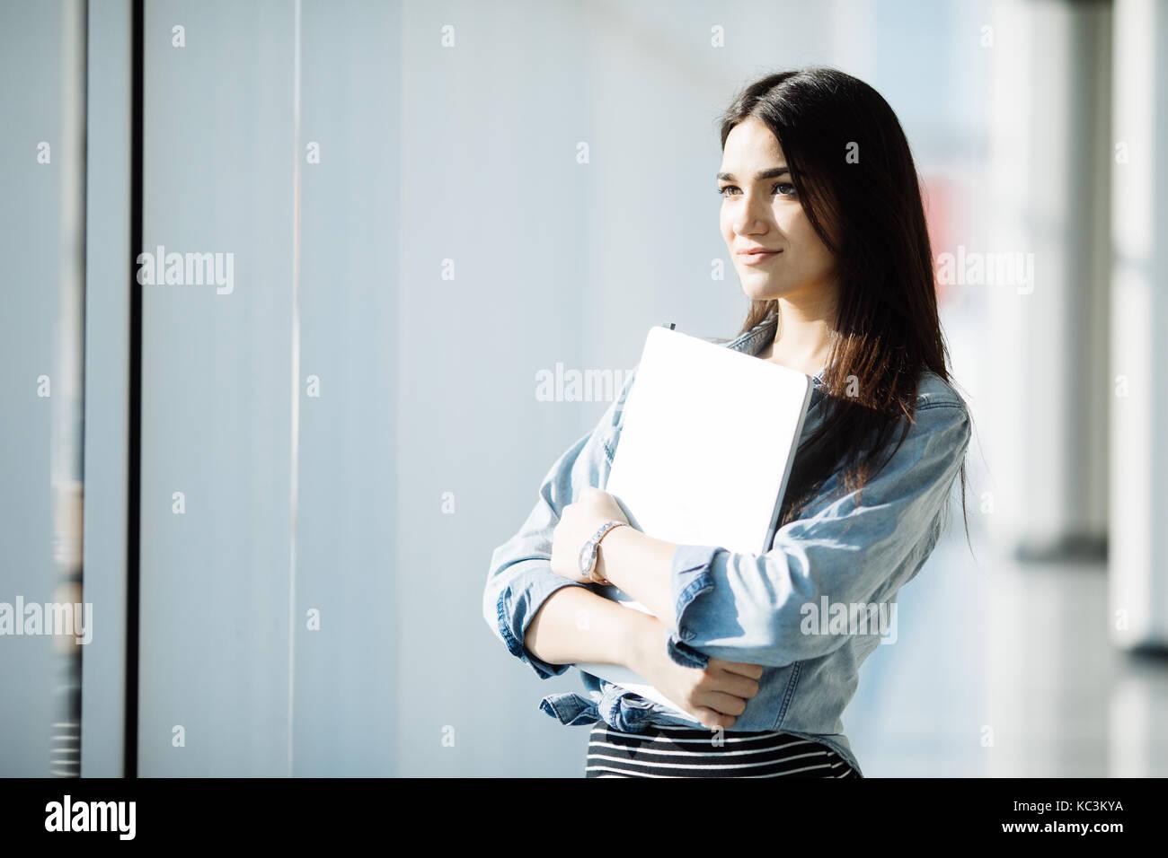 Female office worker réussie avec net-book est debout dans l'édifice, catégorie gratte-ciel intérieur Photo Stock