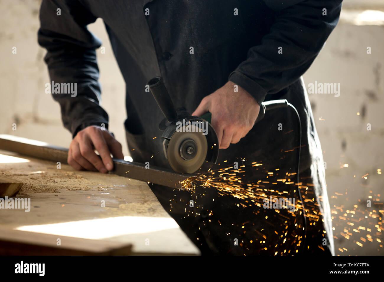 Artisan travaillant avec l'outil électrique en atelier Photo Stock