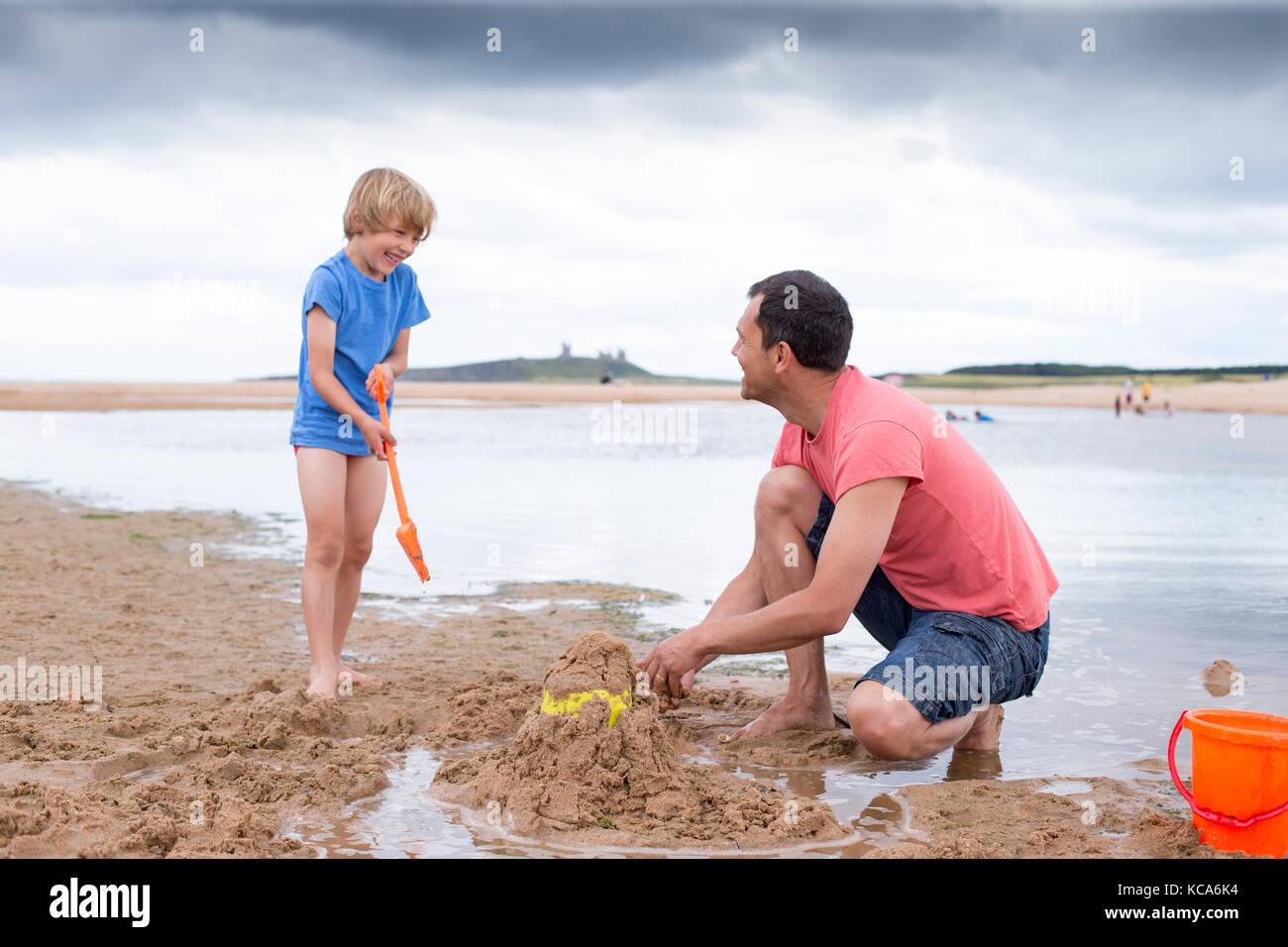 Un père et son fils sont construire des châteaux de sable sur la plage Photo Stock