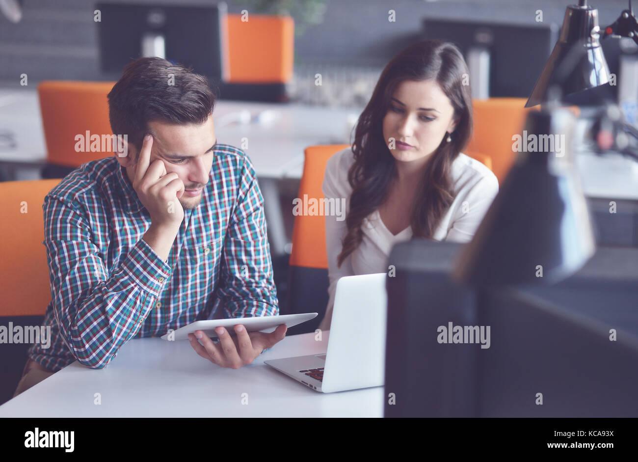 Jeune couple d'affaires occasionnels à l'aide d'ordinateur dans le bureau. coworking, responsable Photo Stock