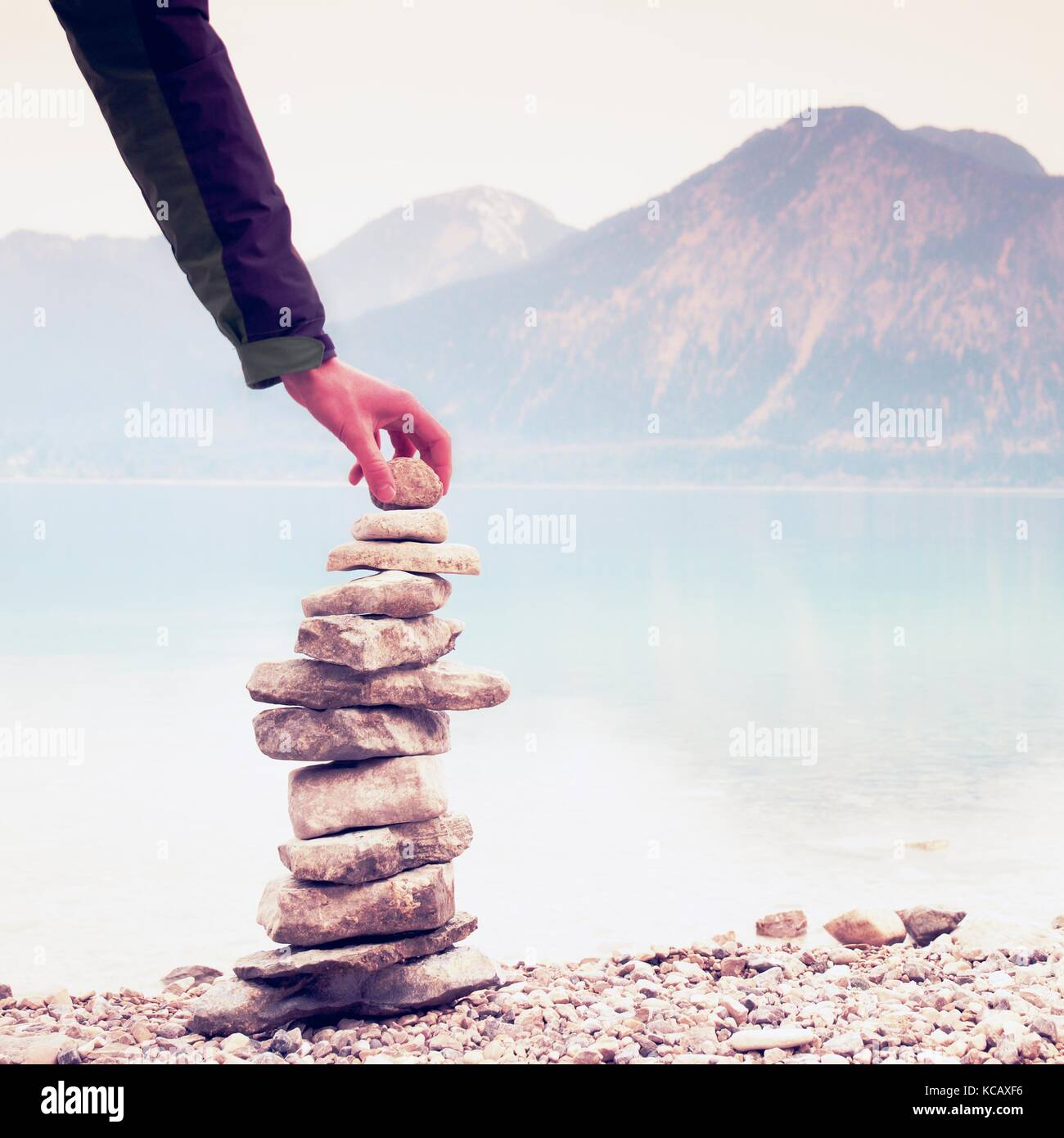 Homme pyramide construite à partir de galets. Pierre pyramide équilibrée sur le rivage de l'eau Photo Stock