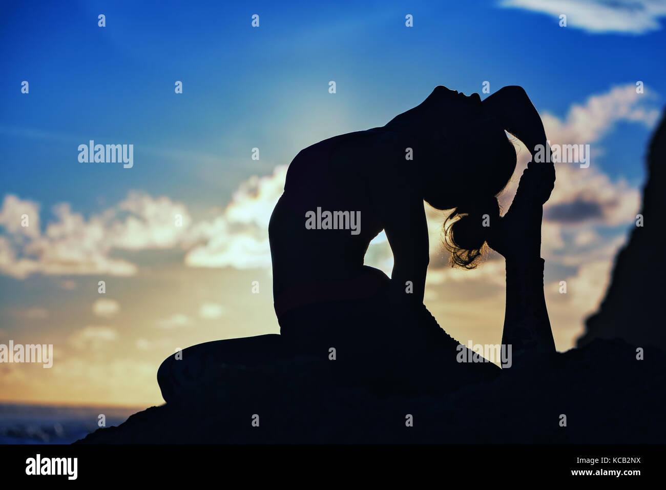 Femme silhouette noire sur fond de ciel coucher. Jeune fille active yoga assis sur la plage de roche, qui s'étend Photo Stock
