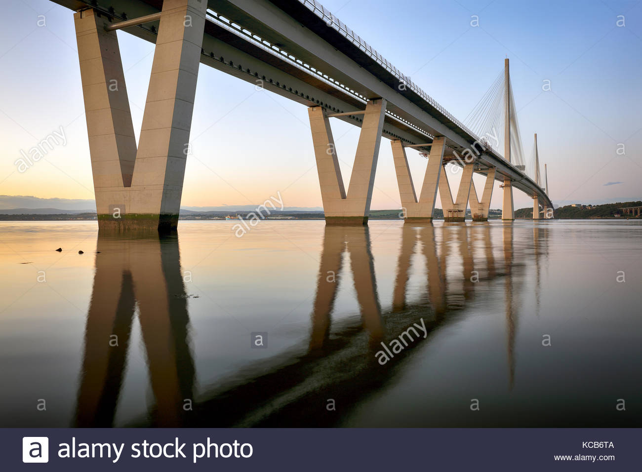 Reflets de la nouvelle Queensferry Crossing bridge sur le Firth of Forth au coucher du soleil. Banque D'Images
