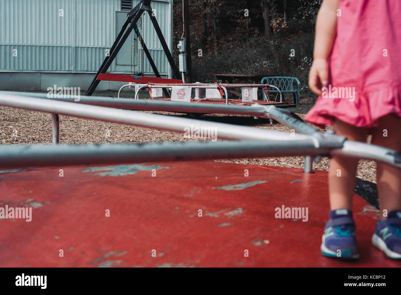 Un bambin se dresse sur un merry go round sur un terrain de faible revenu Photo Stock