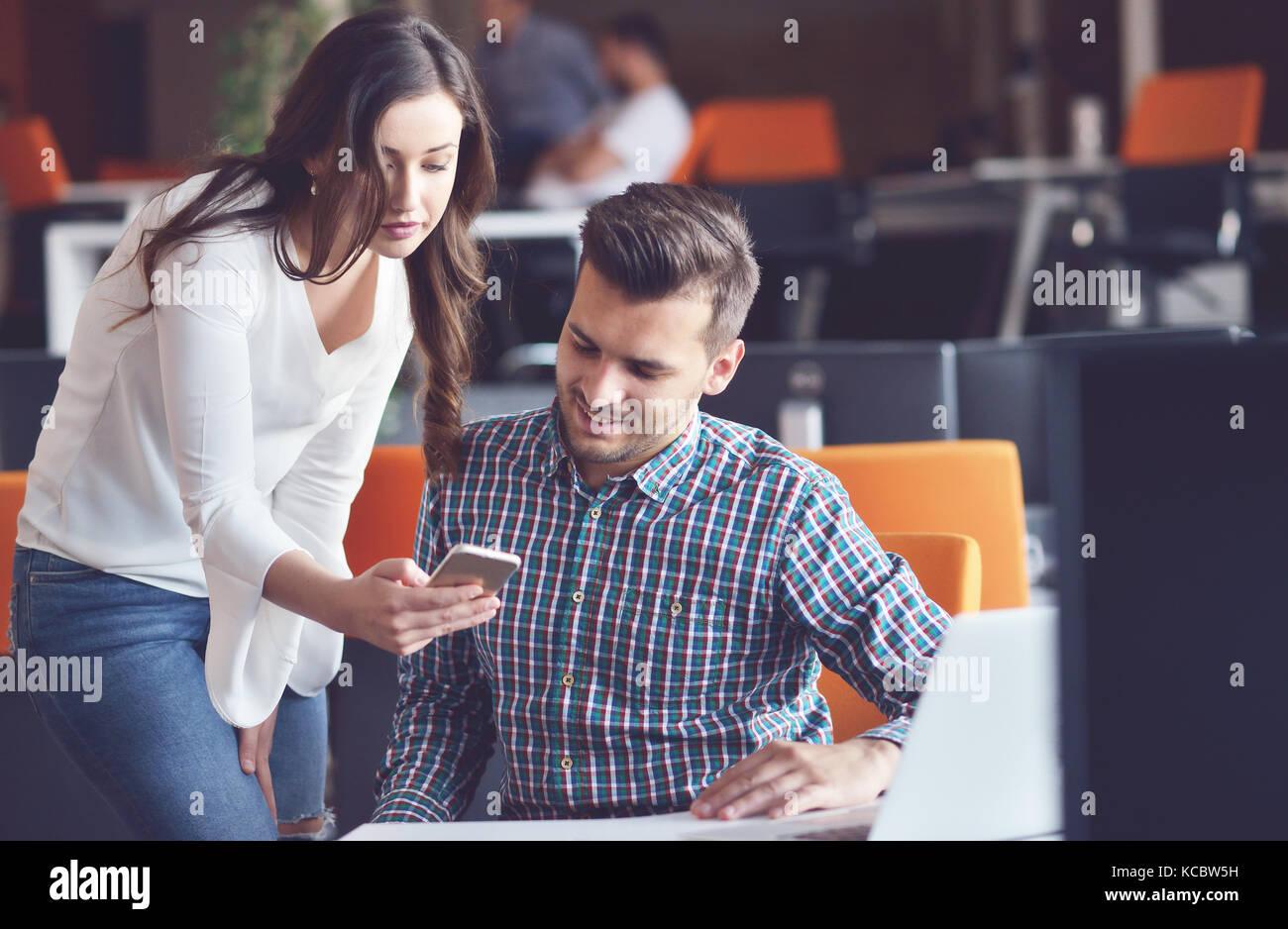 Jeune couple d'affaires occasionnels à l'aide d'ordinateur dans le bureau. coworking, responsable de la création Banque D'Images