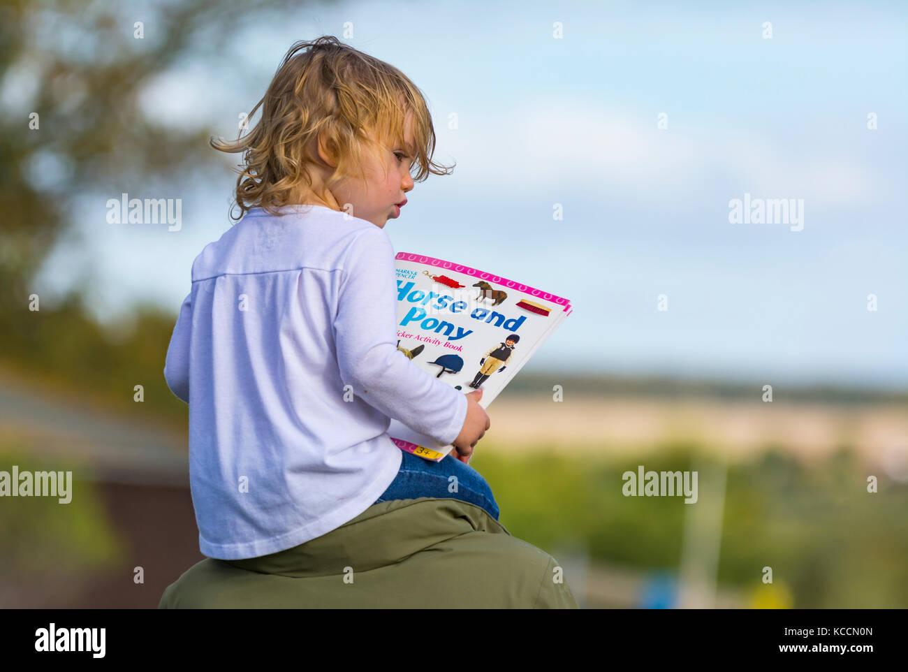 Jeune fille assise sur les épaules de quelqu'un tout en lisant un livre d'enfant. Photo Stock