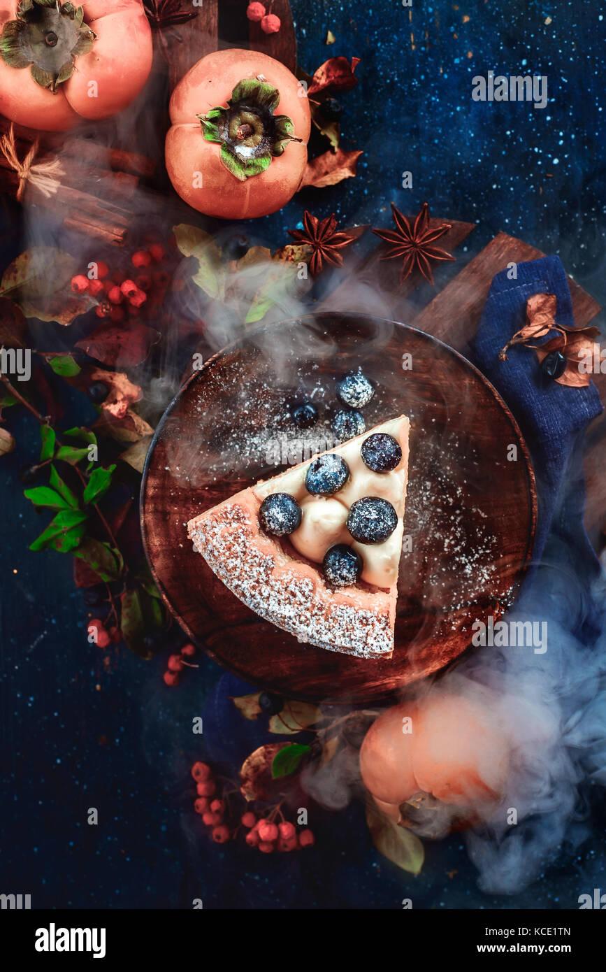 Un morceau de tarte à la citrouille avec les bleuets et le kaki sur un fond de bois foncé avec décor Photo Stock