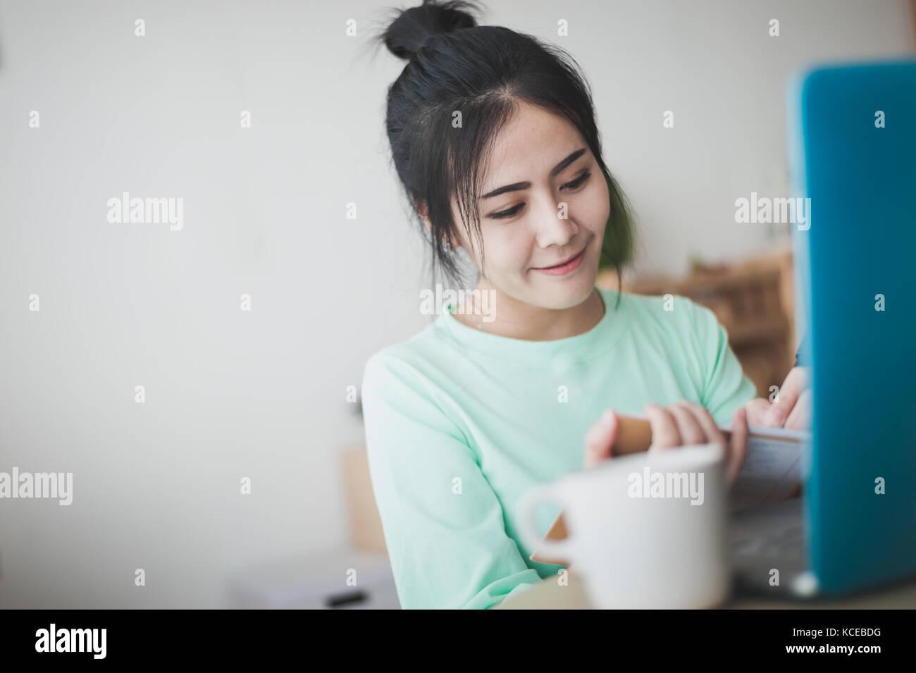 Young attractive asian woman freelancer écrit sur ordinateur portable en main gauche tout en travaillant avec Photo Stock