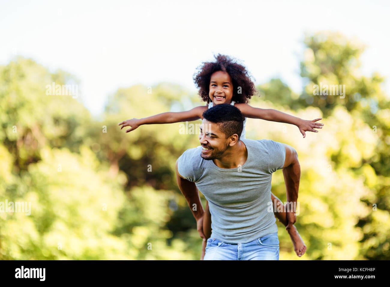 Portrait de jeune fille portant son père sur son dos Photo Stock