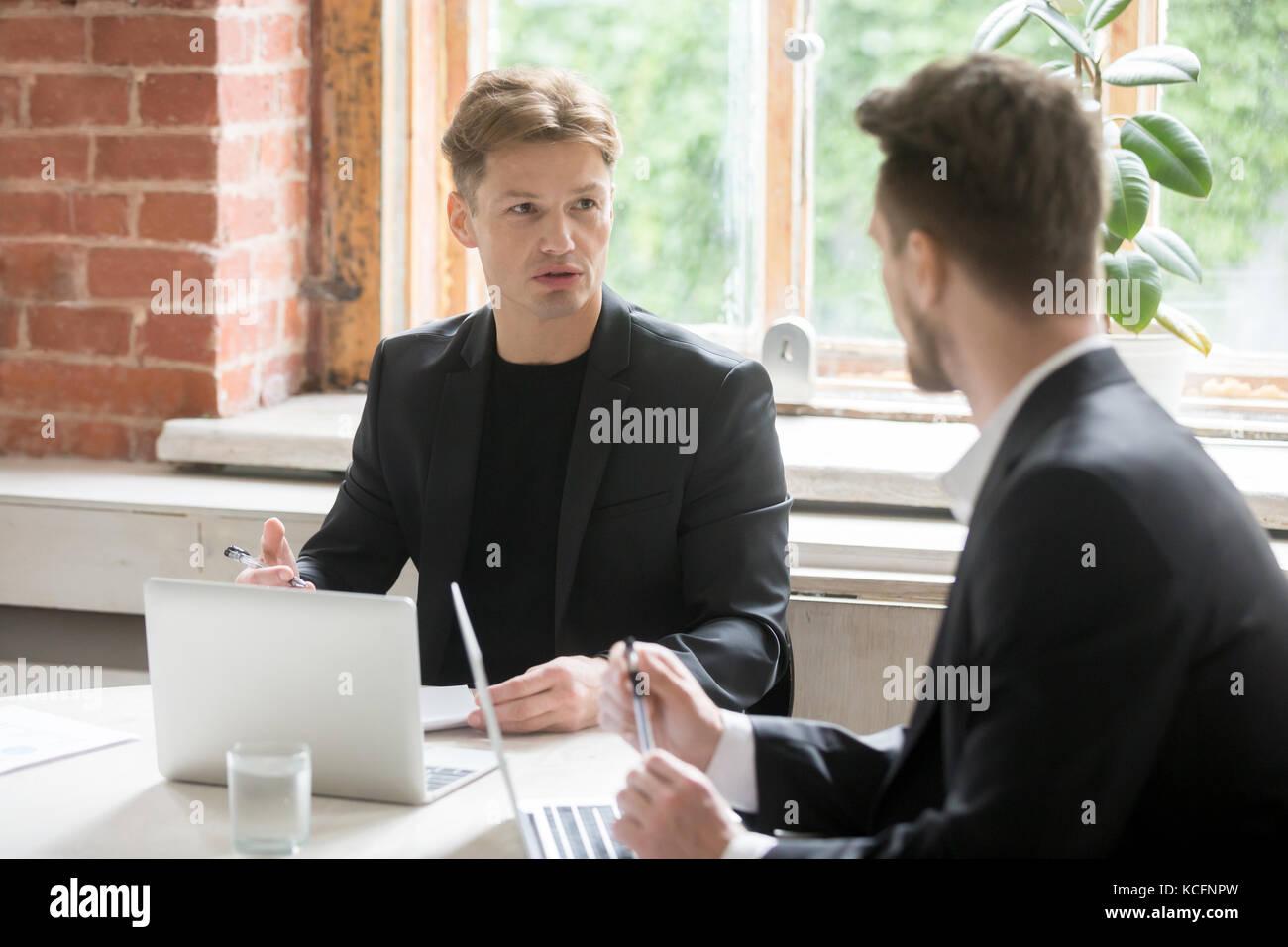 Deux jeunes employés de discuter les objectifs de l'exécutif devant les ordinateurs portables à vert au travail. Banque D'Images