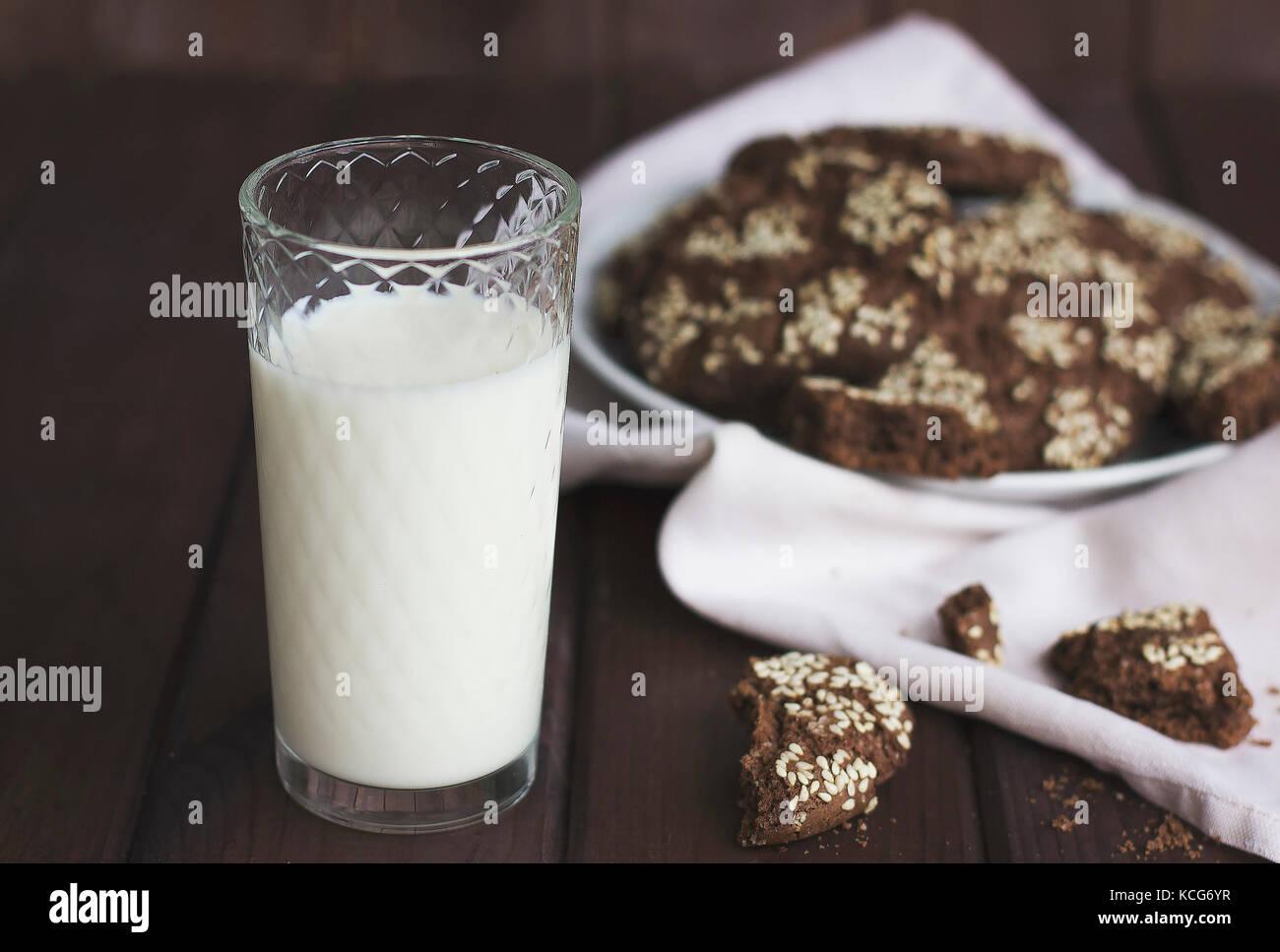 Les cookies au chocolat avec des graines de sésame dans une plaque d'époque et un verre de lait sur Photo Stock