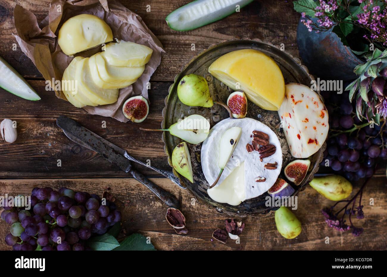 Les différents fromages et fruits sur le fond de bois Photo Stock