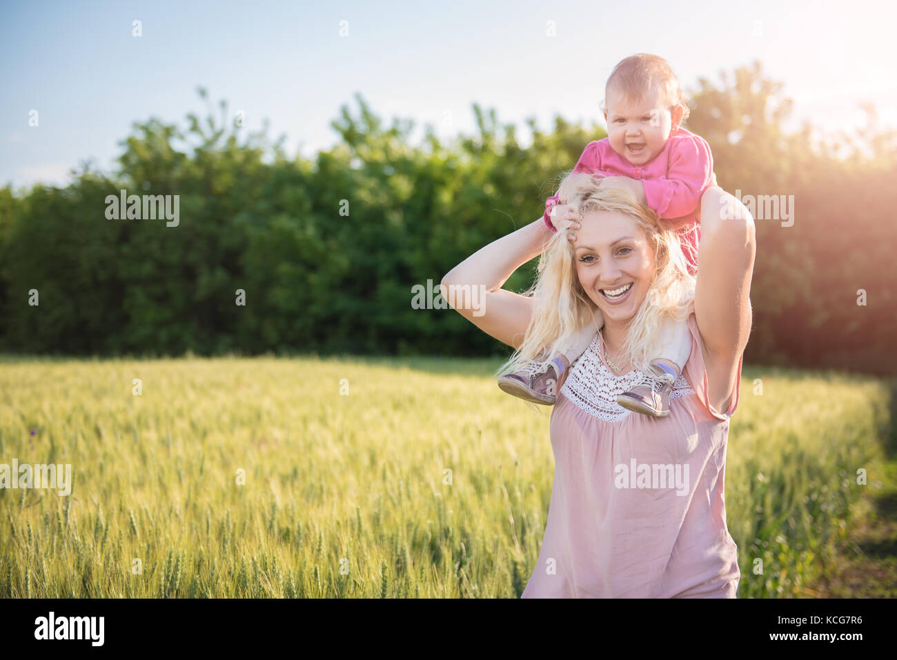 Mère portant sa petite fille Piggyback et Comité permanent par le champ de blé Photo Stock