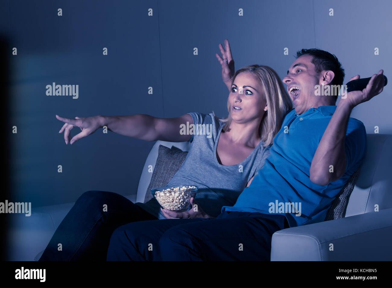 Peur couple watching film d'horreur à la maison Photo Stock