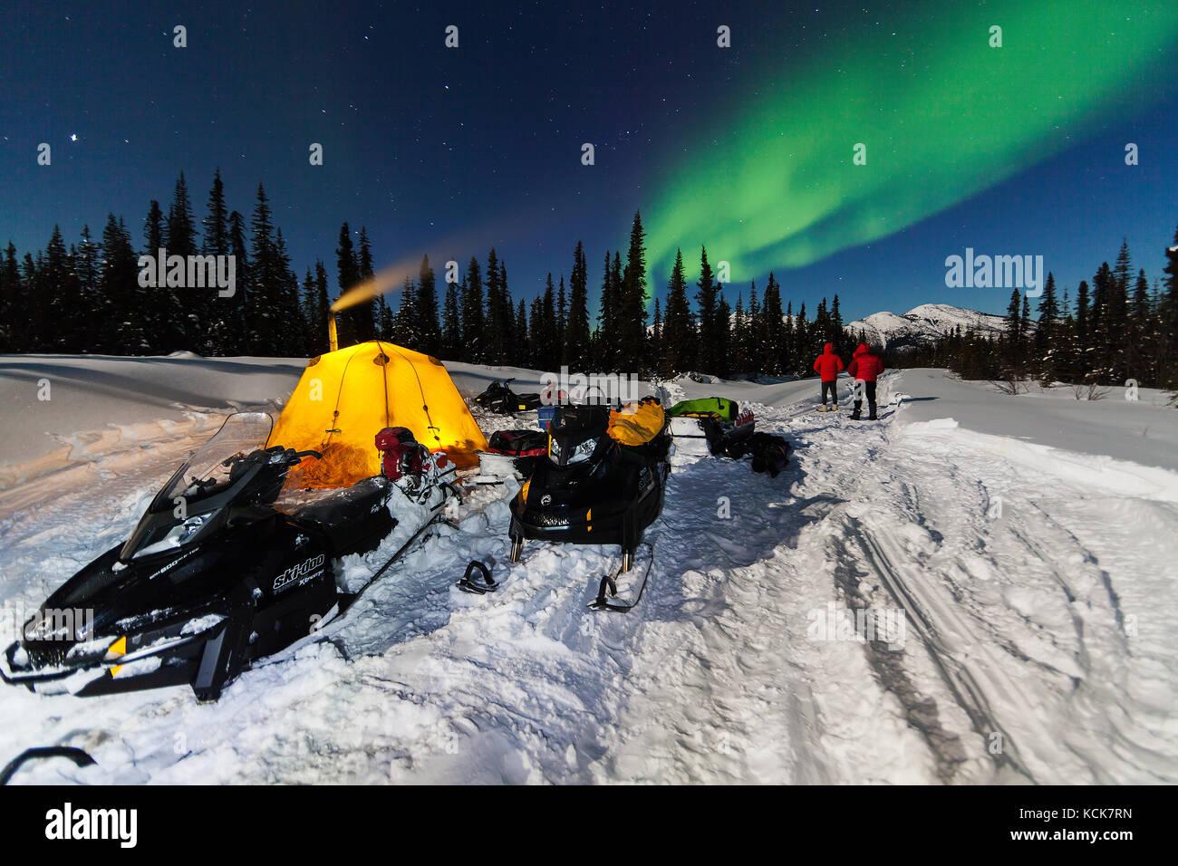 Les motoneigistes campé pendant la nuit sont accueillis avec northern lights en voyageant le long du sentier Photo Stock