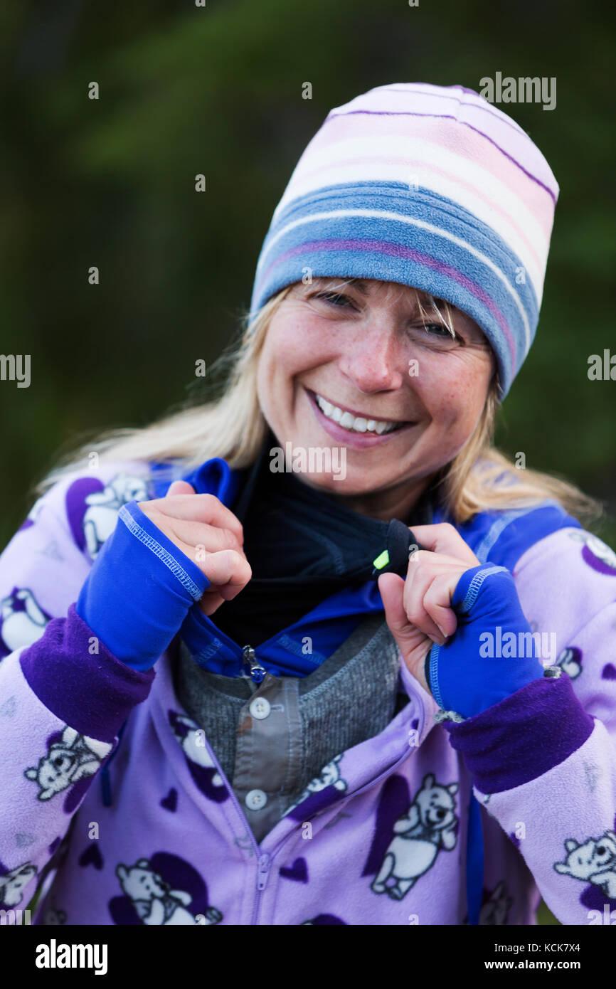 Une femme habillée de couleurs vives camping-partage un rire alors qu'elle décrit ses nombreuses couches Photo Stock