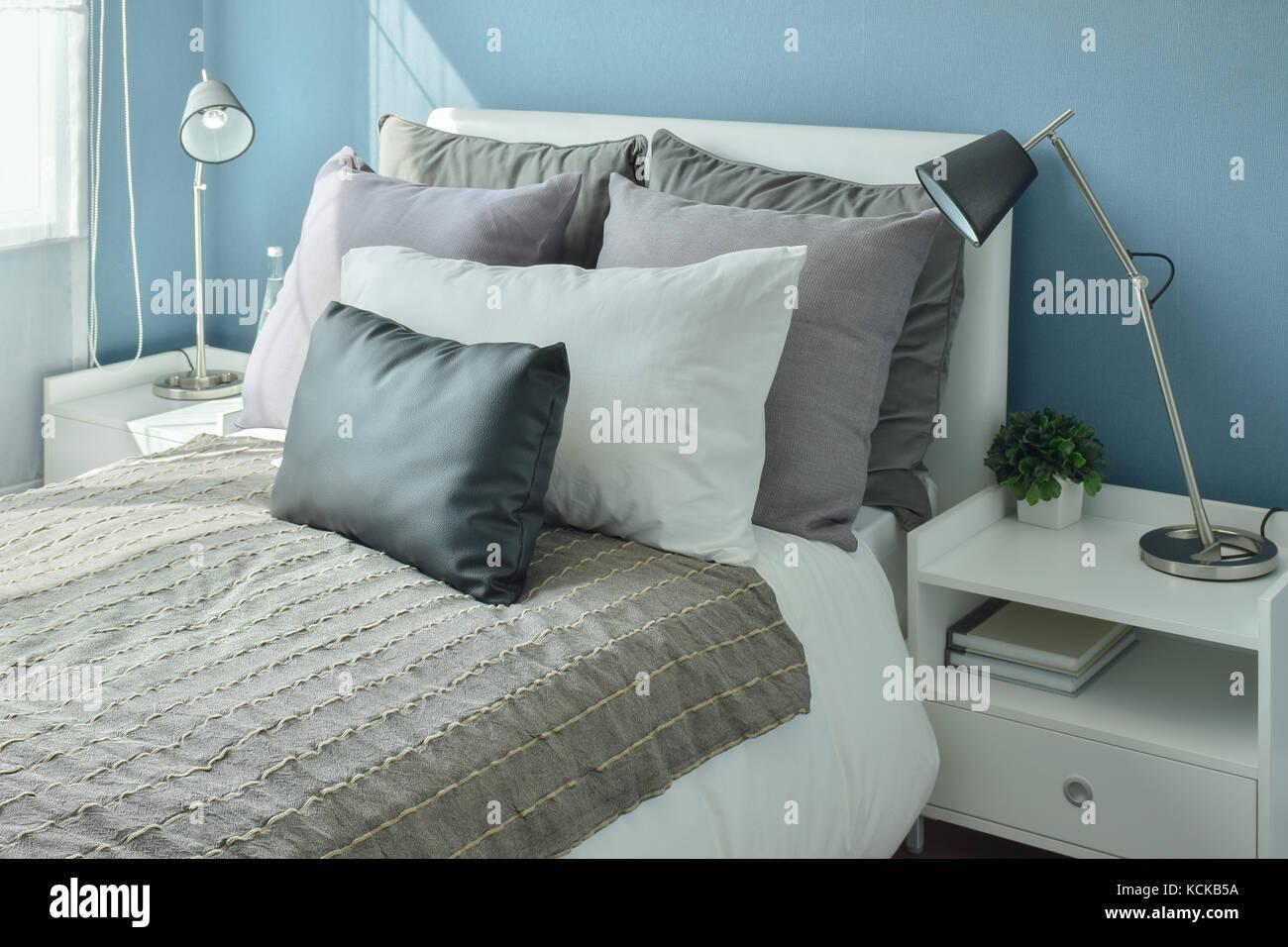 Gris clair, gris foncé et beige des oreillers au lit avec ...