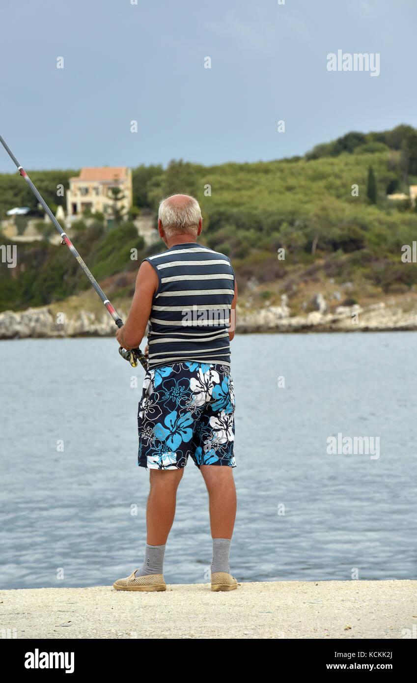 b50fbd1d21 Un homme pêche sur un mur du port sur l'île grecque de Corfou près de  kassiopi floery portant des shorts bleu, des chaussettes et des sandales.