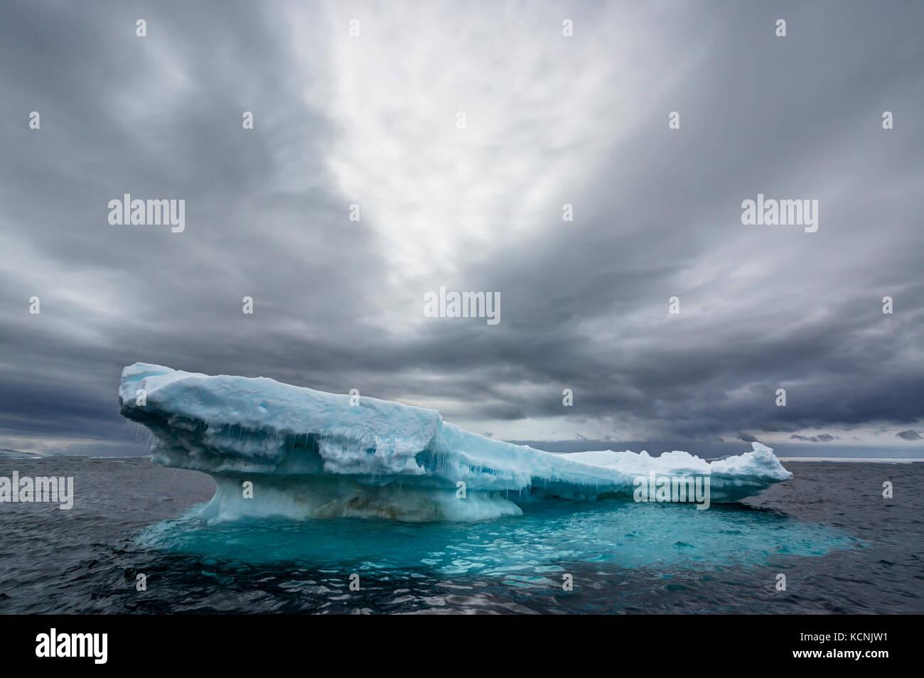 Un iceberg flottant lentement fait place à l'océan attaque inévitable sous un ciel dramatique Photo Stock
