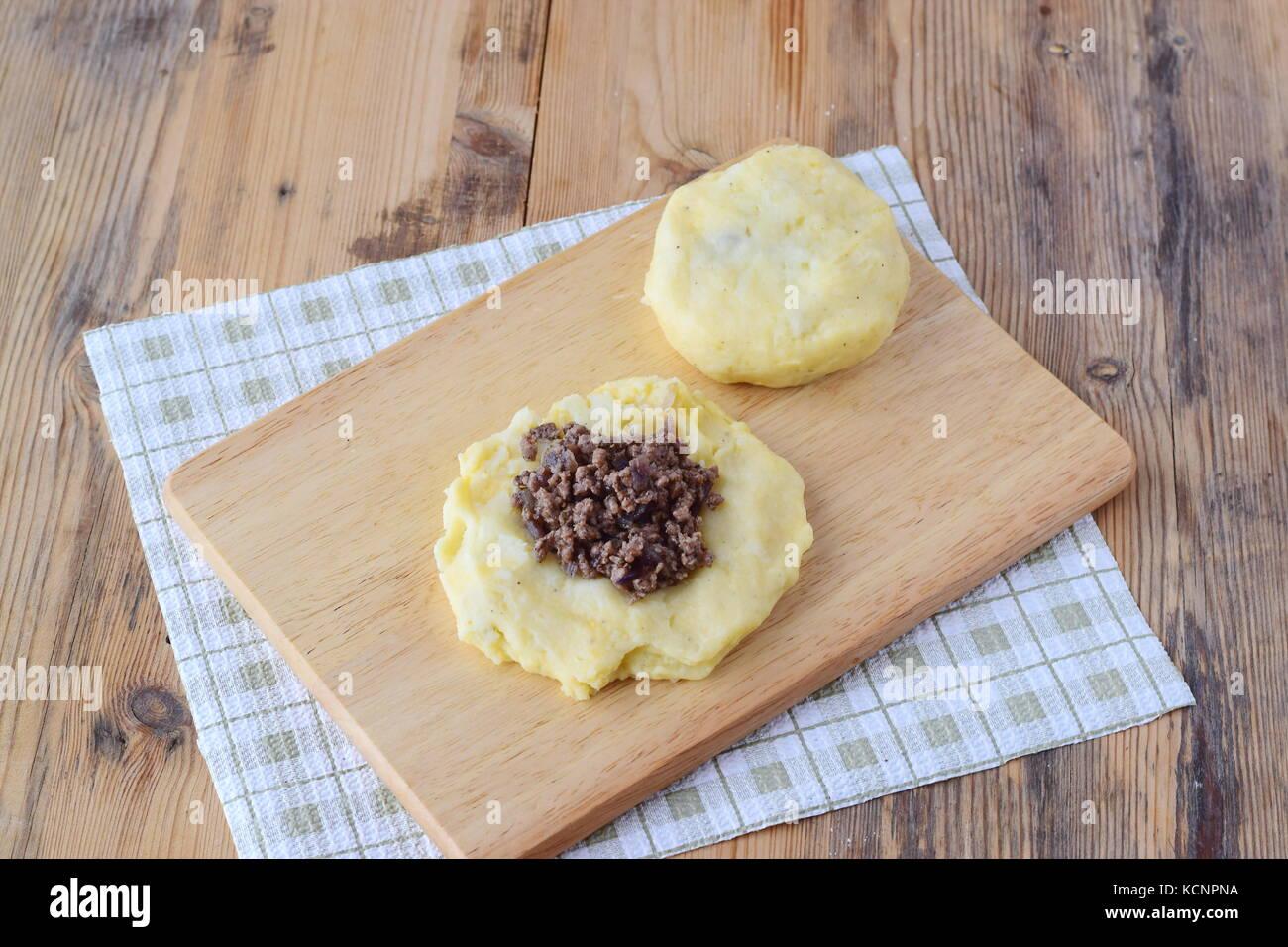 Boulettes de pommes de terre farcies à la viande hachée sur une planche à découper en bois. Photo Stock