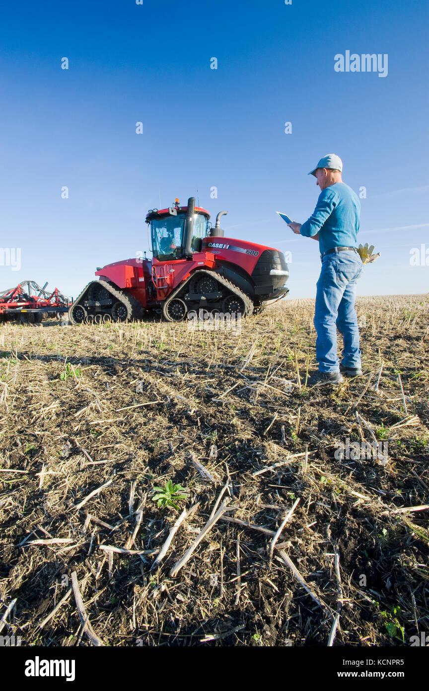 Agriculteur en utilisant une tablette en avant d'un tracteur et semoir pneumatique, les semis de blé d'hiver Photo Stock