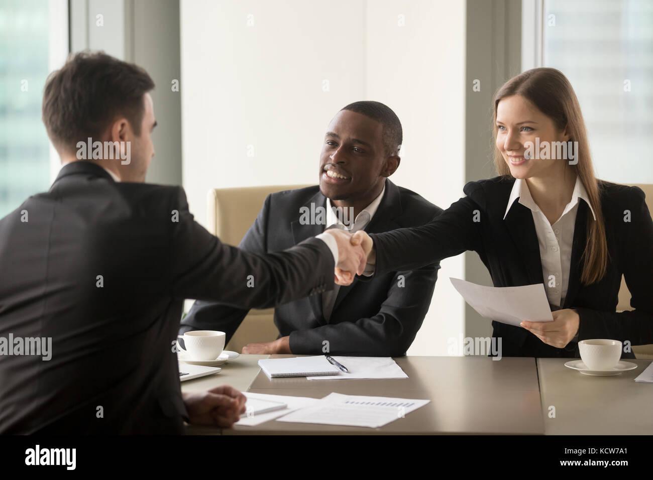 Smiling businesswoman handshaking avec partenaire au début de négociations multinationales. afro-américain Photo Stock
