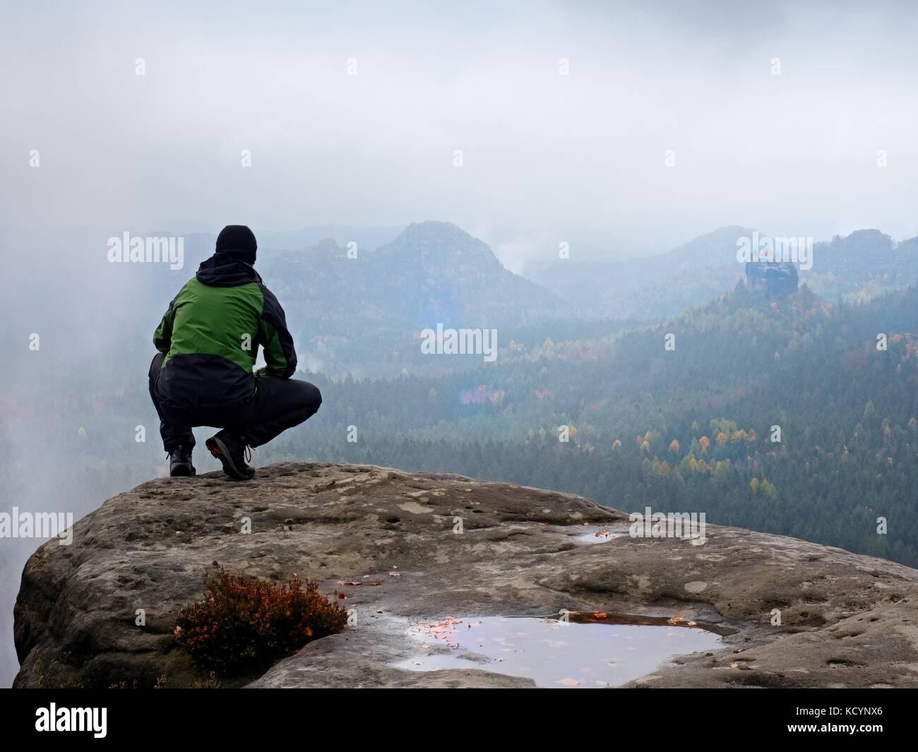 Touriste à tête rouge et vert noir sportswear en position accroupie sur un rocher, profitez de l'automne Photo Stock
