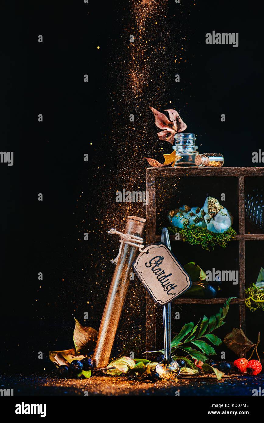 Mystic Nature morte avec un tube à essai de Stardust et la caisse en bois avec des objets magiques et d'ingrédients de potion. sorcier ou une sorcière table avec poussière de lutin. conte de concept avec fond sombre et copiez l'espace. Banque D'Images