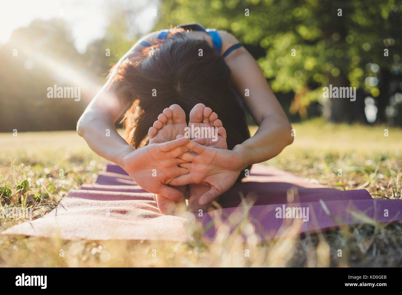 Femme mature dans le parc, assis, stretching, in yoga position Photo Stock