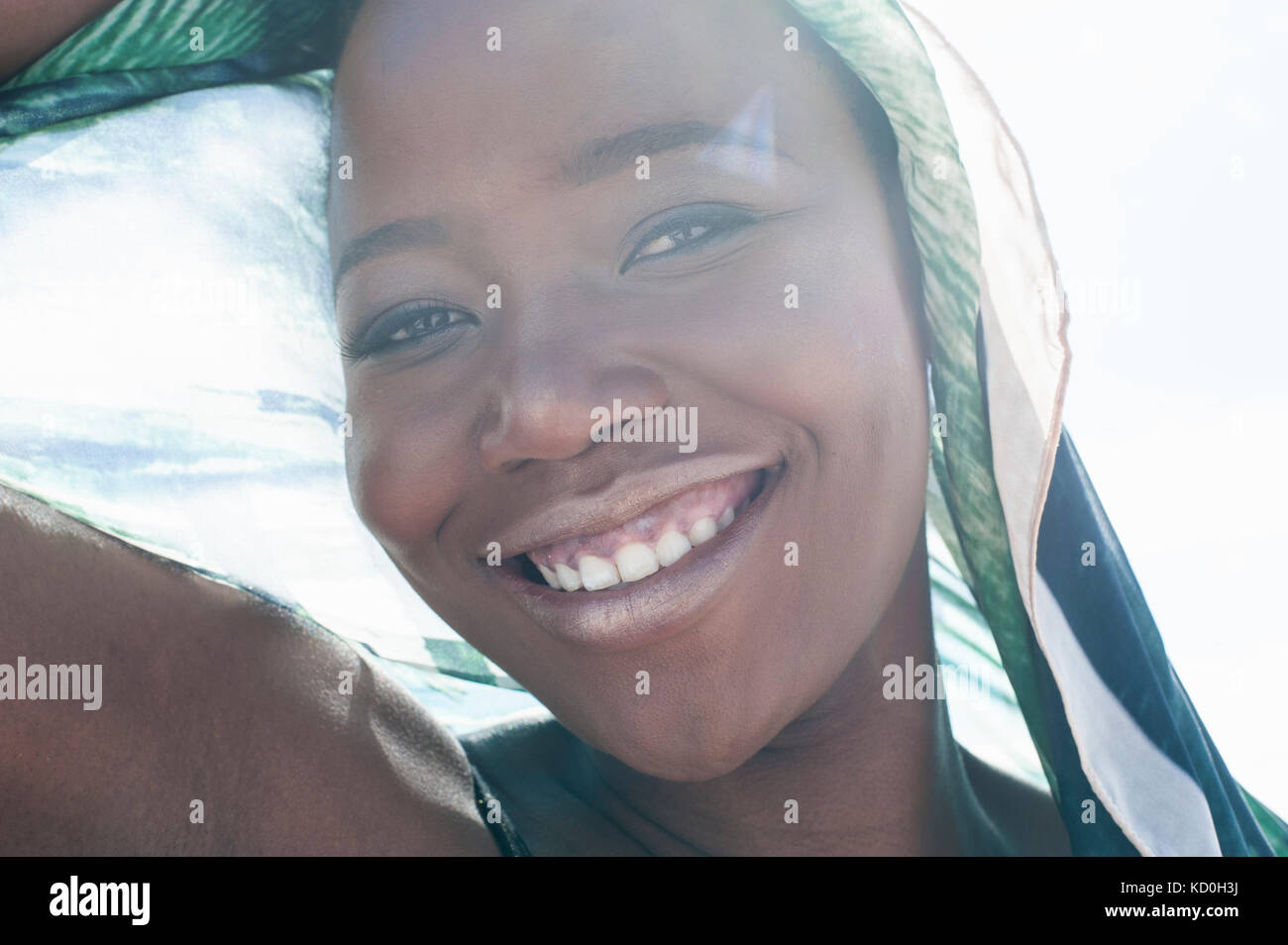 Portrait of young woman on beach, smiling, foulard dentelle drapée autour d'elle, close-up Photo Stock
