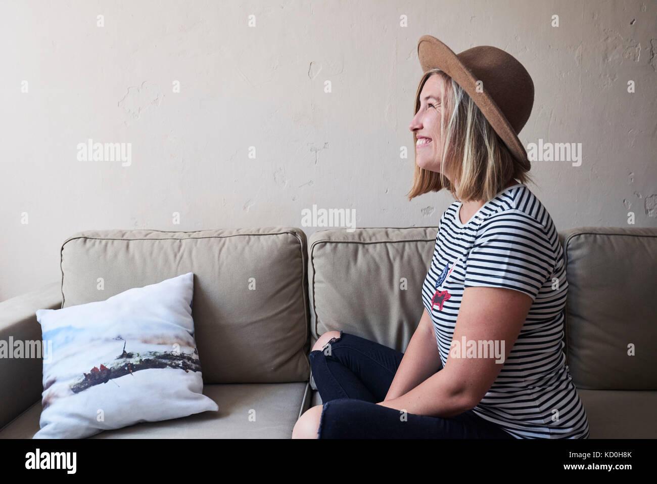Femme assise sur un canapé, smiling, portrait Photo Stock
