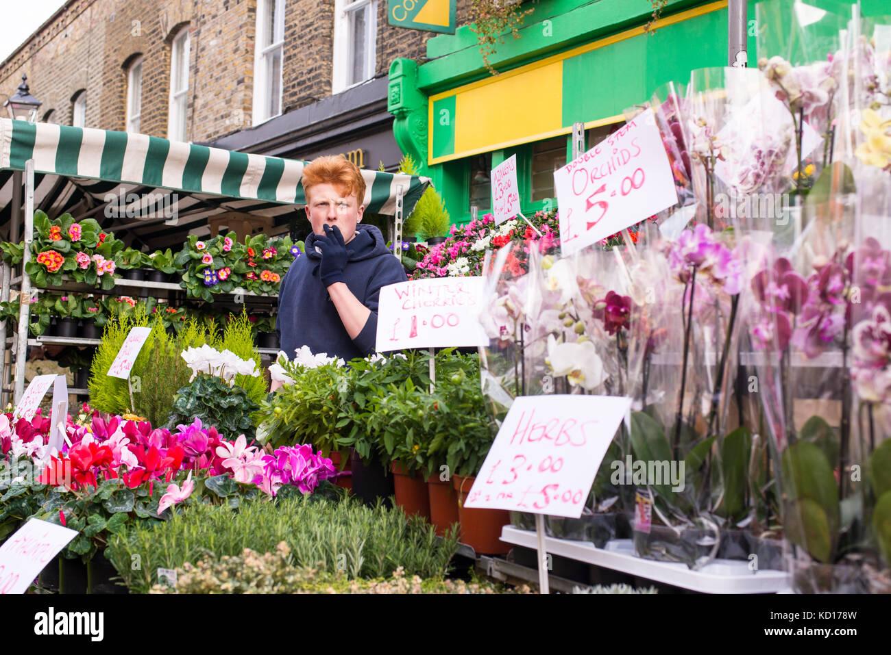 Jeune homme vente de fleurs et plantes dans une piscine au célèbre Columbia Road Flower Market, près Photo Stock