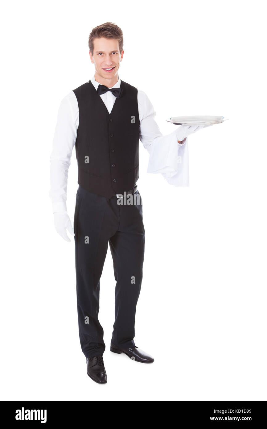 Young waiter standing avec couvercle cloche sur fond blanc Photo Stock
