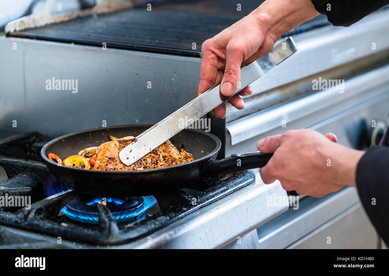 Le poisson dans la poêle chef tournant pendant la cuisson Photo Stock