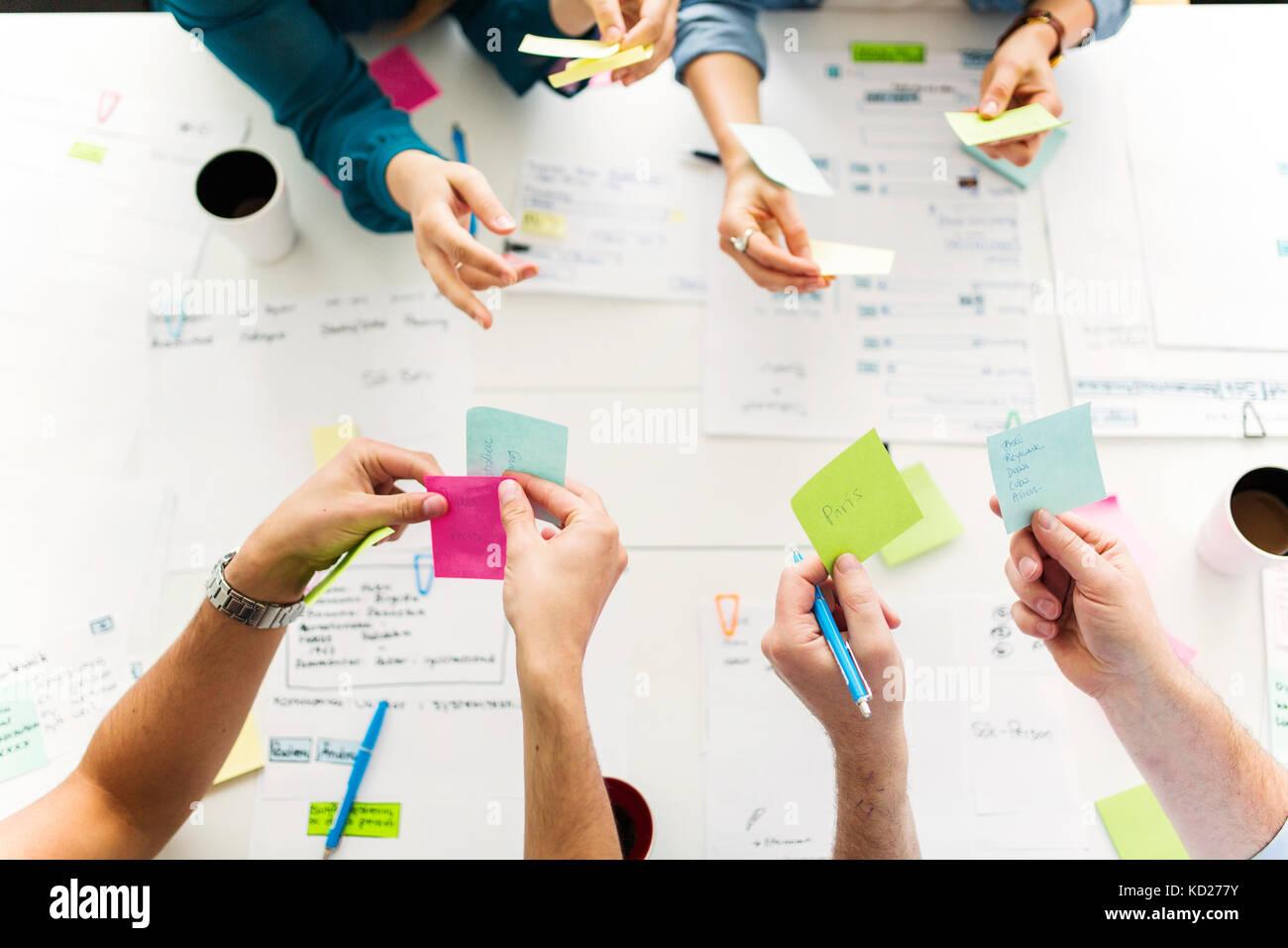 À l'aide de collègues notes adhésives au cours de réunion d'affaires Photo Stock