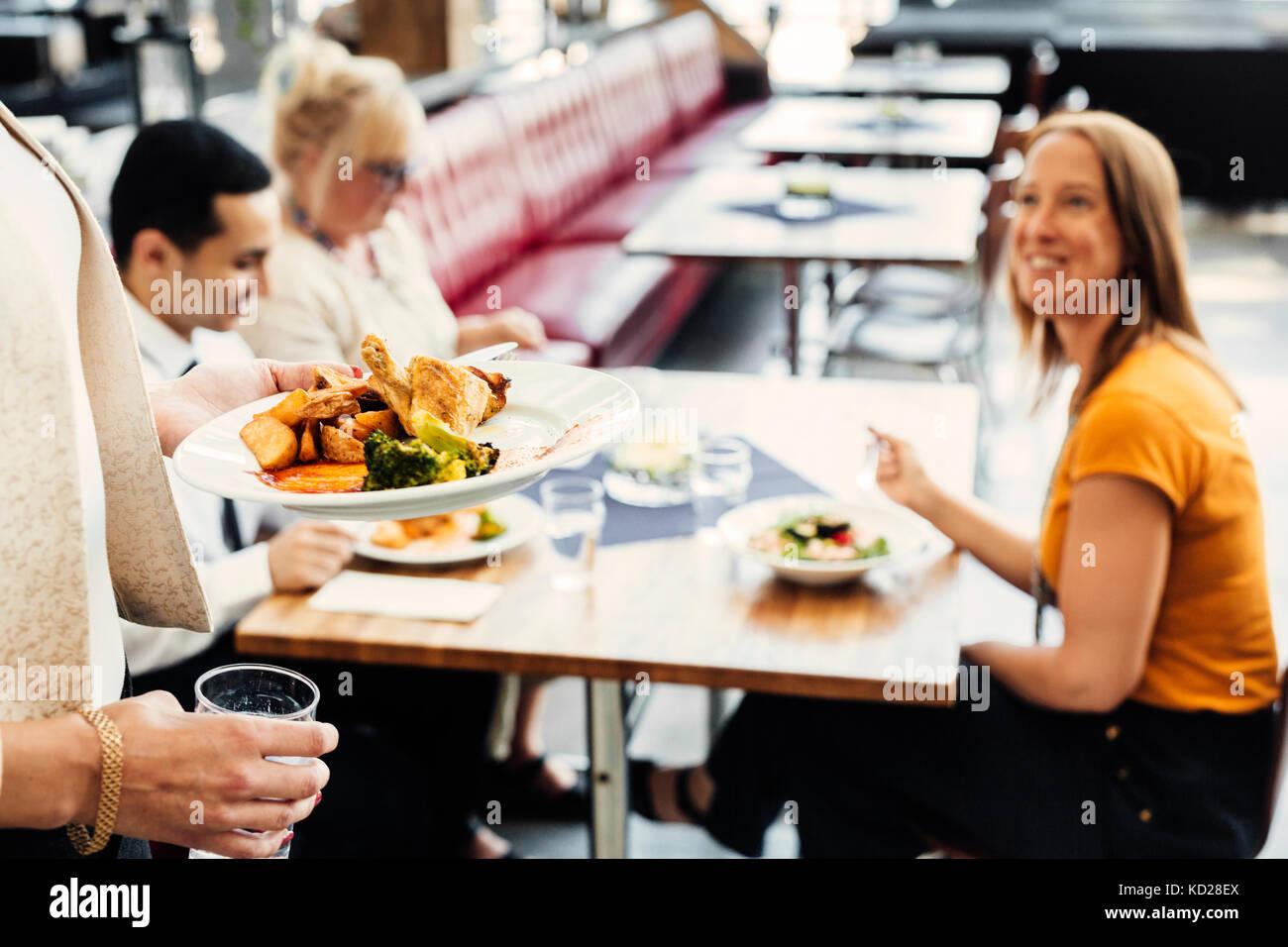 Quatre collègues réunion pendant le déjeuner dans une cafétéria Photo Stock