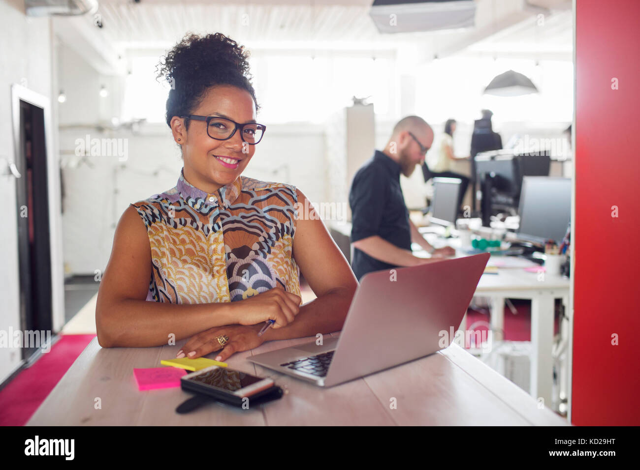 Smiling woman using laptop, collègues en arrière-plan Banque D'Images