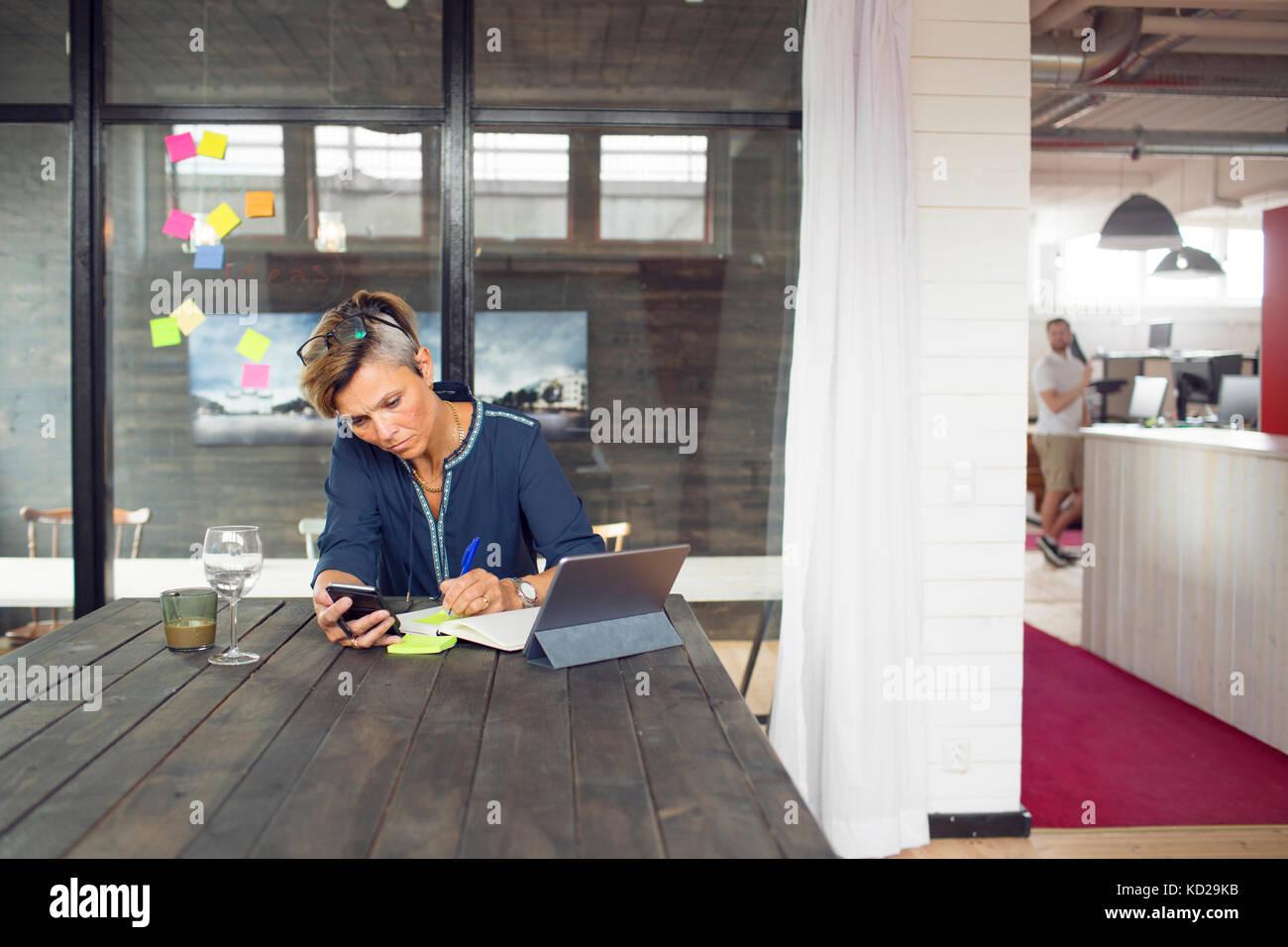 Femme textos par table Photo Stock
