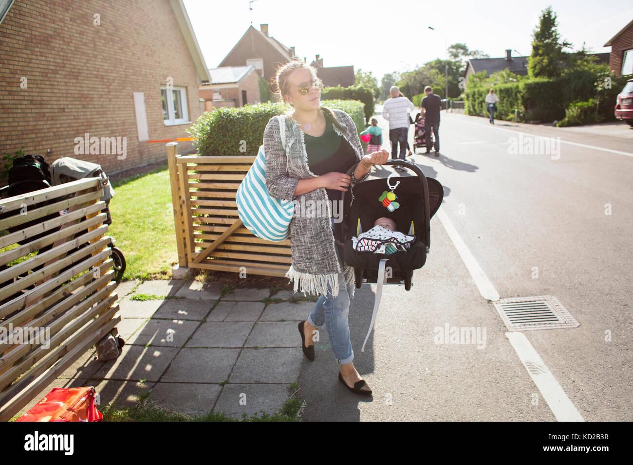 Mère portant son (0-1 mois) en siège auto portable Banque D'Images