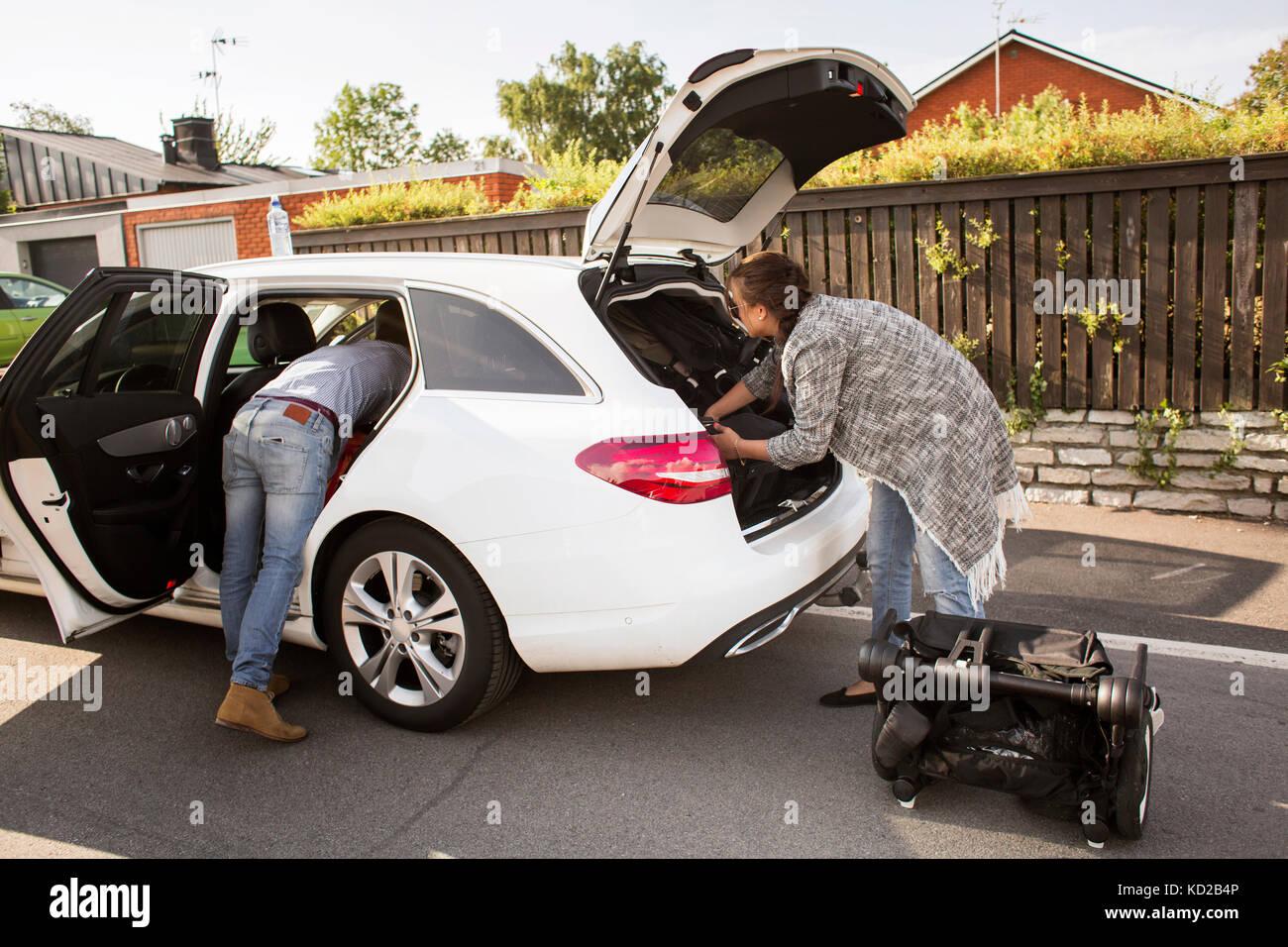 L'homme et la femme l'emballage assurance en voiture Banque D'Images