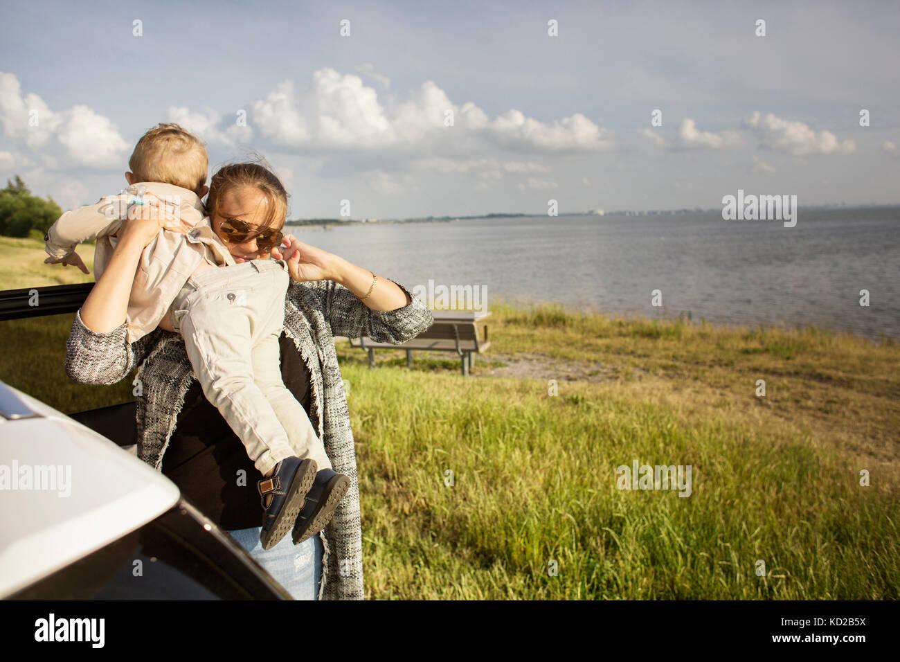 Mère tenant son (18-23 mois) par la mer Banque D'Images
