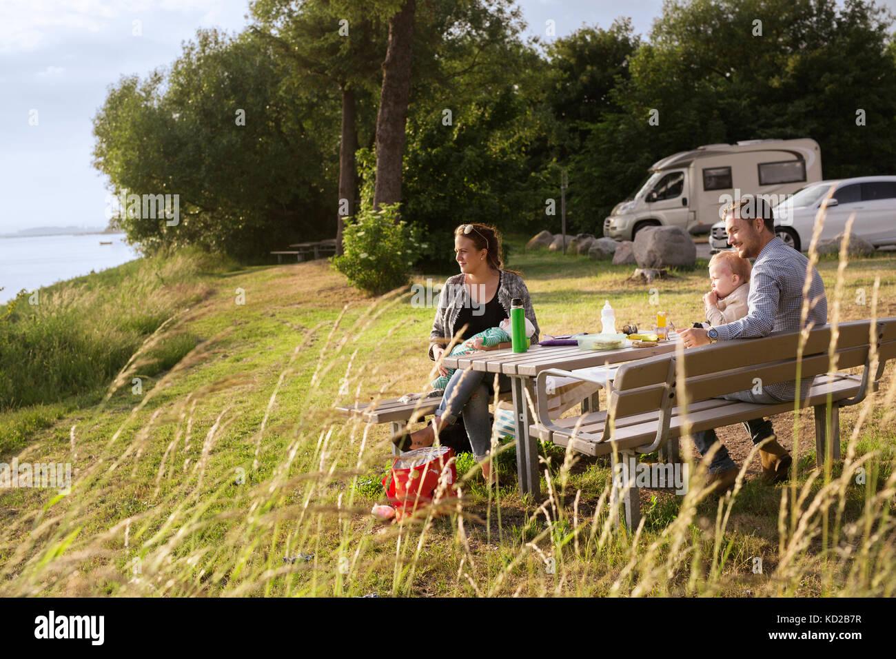 Les parents avec enfants (18-23, 0-1 mois) assis par table de pique-nique Banque D'Images
